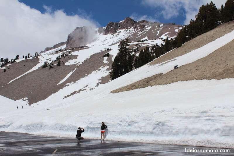 Turistas brincando com a neve no estacionamento do Lassen Peak