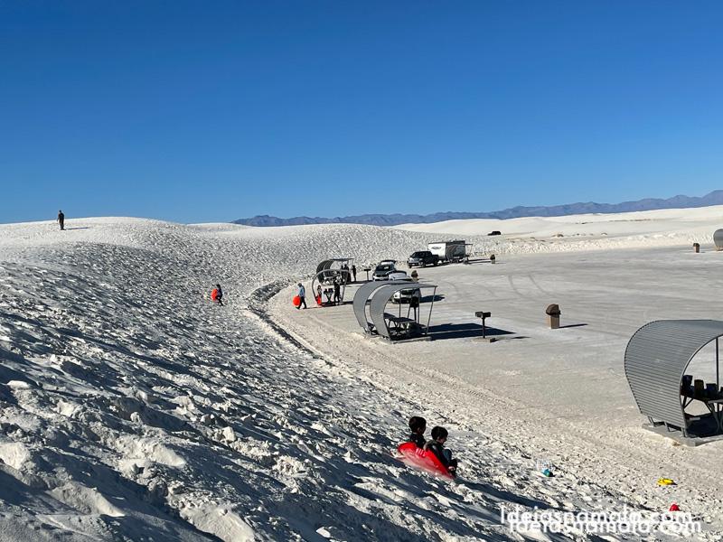 Crianças descendo as dunas de areia no Novo Mexico